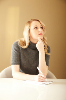 photo shows a job seeker thinking about her list of actions she needs to do to find a new job